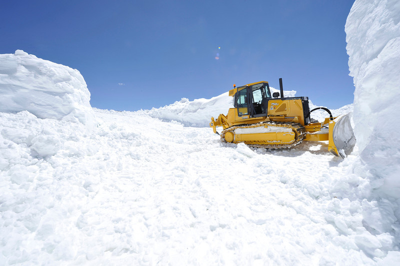 Walt Hester | Trail Gazette<br /> A bulldozer sits in a gap between the Fall River store, right, and its diesel generator, at the top of the Old Fall River Road on Friday. The park has recieved so much snow that officials have said the old road will not open for Independence Day, and due to the inevitable maintainence, may not open this year.