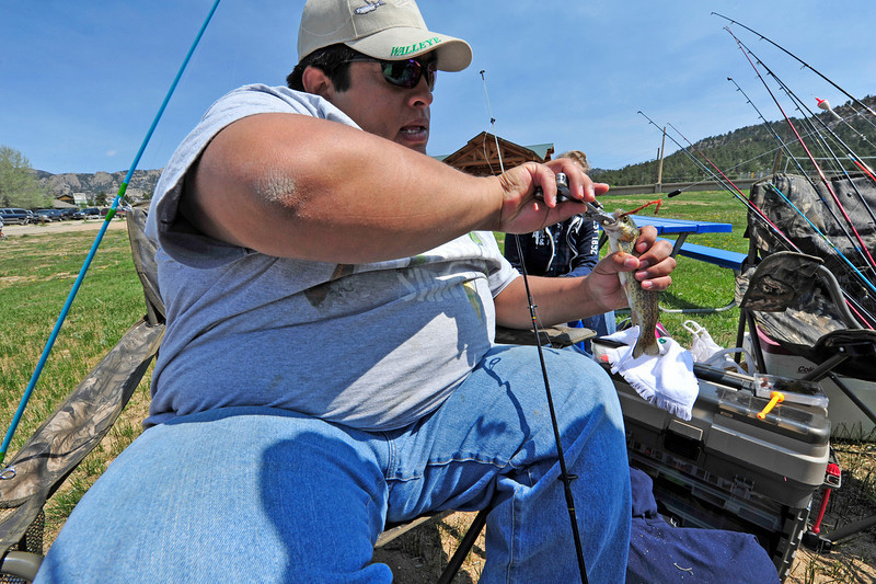 Walt Hester | Trail Gazette<br /> Clyde Martinez of Aurora removes a hook from a fish caught in Lake Estes on Saturday. Fishing enthusiasts descended on Estes Park for the annual Fishing Derby on Saturday.