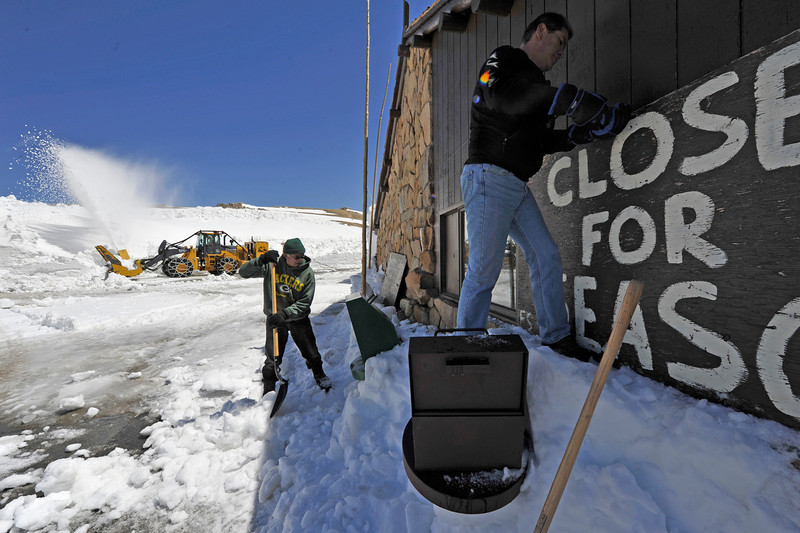 Walt Hester | Trail Gazette<br /> While plows clear the lot, employees of the Trail Ridge Store work hard to ready the store for the season. Park officials hope to official open the road on Friday.