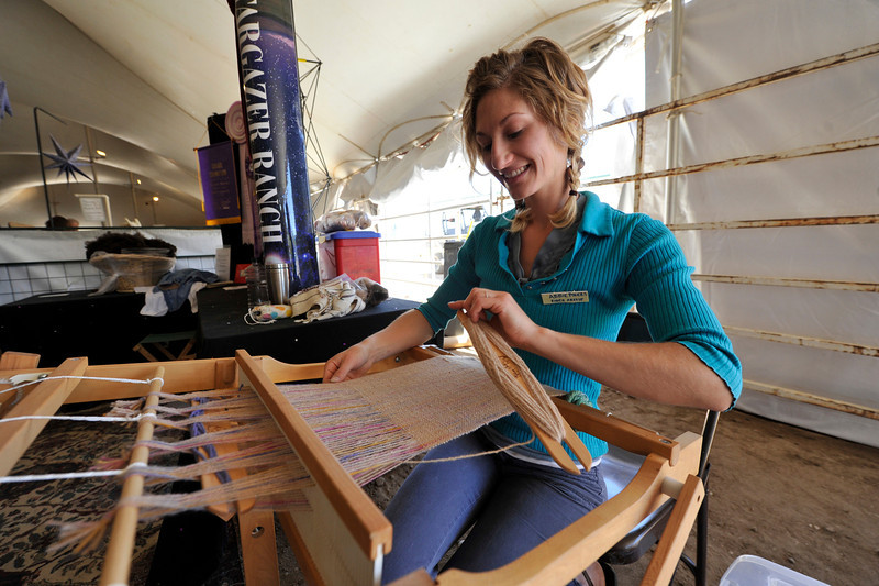 Walt Hester | Trail Gazette<br /> Loveland fiber artist Abbie Powers demonstrates her creativity at the annual Wool Market on Sunday in close quarters with the source of her medium. Every step of the woolen product process was represented at the market.