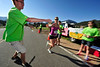 Walt Hester | Trail Gazette<br /> Jeff Switzer, 15, hands water to Ruby Bode at aid station 3 at Peak View Drive and Mary's Lake Road during Sunday's Estes Park Marathon. Bode went on to set a new women's marathon course record on record.
