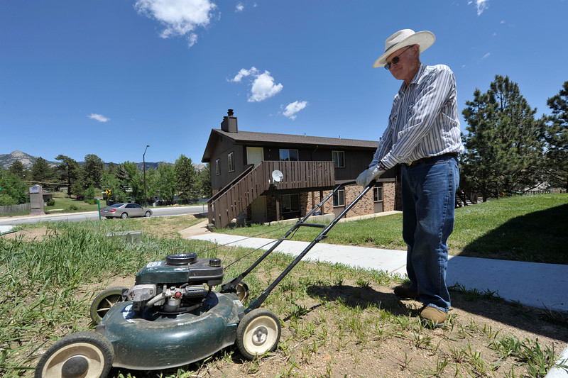 Walt Hester | Trail Gazette<br /> Ken Hale pushes a lawn mower around a yard along Prospect Avenue on Wednesday. The sunshine and warmth made for a perfect lawn-work day.