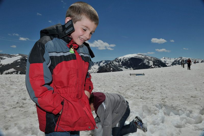 Walt Hester | Trail Gazette<br /> Caleb Peters of Wylie, Texas is bundled but happy in the snow at Forest Canyon Overlook on Wednesday. Peters and family spent a few moments throwing snowballs and posing for pictures before heading back to the relative heat of Estes Park.