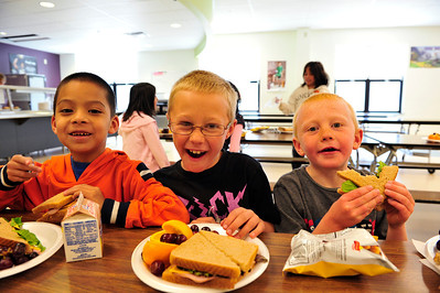 Walt Hester | Trail Gazette David Dominguez, 7, Landon Donaldson, 7, and Aidan Donldson, 6, enjoy lunch at the Kids' Cafe on Tuesday. The cafe is held at the Estes Park Elementary School.