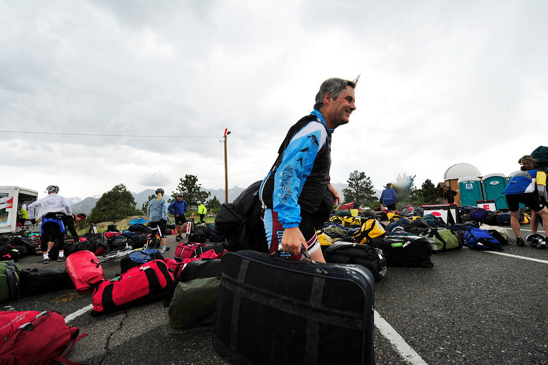 Walt Hester | Trail Gazette<br /> Estes Park's Bill Murry picks up his luggage for the day before finding his tent on Sunday. The Tour of Colorado transports riders' luggage from one stop to the next each day.