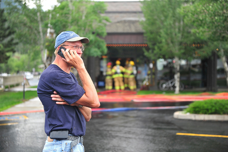 Walt Hester | Trail Gazette<br /> Joe Switzer, maintainance manager for the Stanley Village, relays information while firefighters investigate smoke in the Reel Mountain Theater on Wednesday. Tentitive reports indicate a ventilation fan on the theater's roof overheated creating smoke, but doing no real damage.