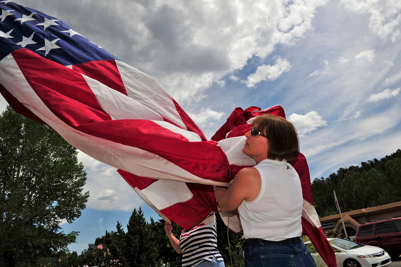 Walt Hester | Trail Gazette<br /> Cheryl Klink helps unfurl a flag at the Coolest Car Show in Bond Park on Monday. The car show also featured a pair of Doug Klink's restored fire trucks, including his snorkle truck which held the flag.