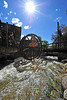 Walt Hester | Trail Gazette<br /> High water of the Fall River pushes the famous water wheel before diving under Elkhorn Avenue on Sunday. The unusually high snow pack has kept rivers high through June and into July.