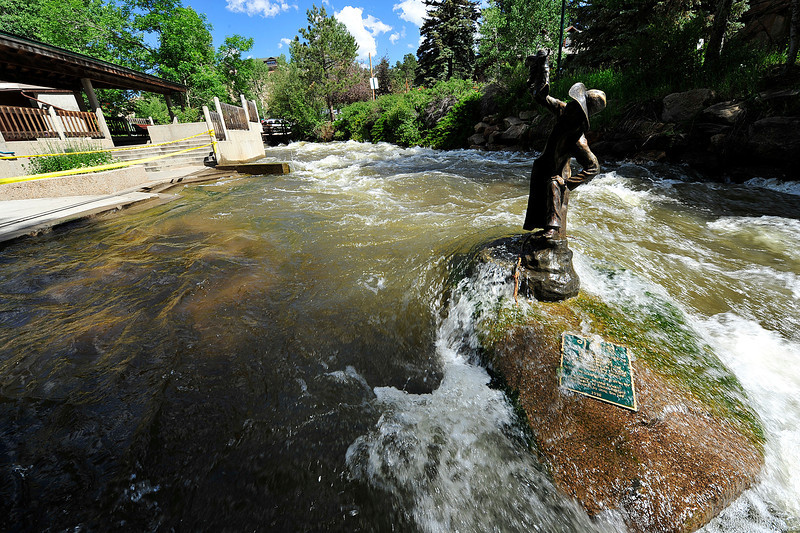 Walt Hester | Trail Gazette<br /> High water runs over steps and statues in Tregent Park on Sunday. The Colorado Department of Water Rescources believes the worst has passed, with peak flow measured on Friday, July 1.