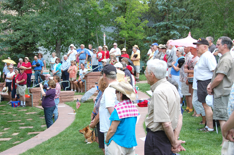 Those attending the July 2 freedom rally in Performance Park in downtown Estes Park stand for the national anthem.