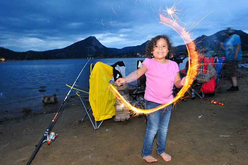 Walt Hester | Trail Gazette<br /> Sophie Falagrady, 6, of Greeley delights in her sparkler on Lake Estes on Monday. Visitors start their fireworks early along the lake's edge.