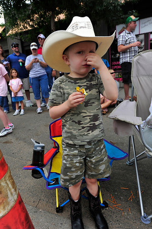 Walt Hester | Trail Gazette<br /> Joshua Basel, 5, of Estes Park does not enjoy the horses, or their byproducts, after the Rooftop Rodeo Parade on Tuesday.