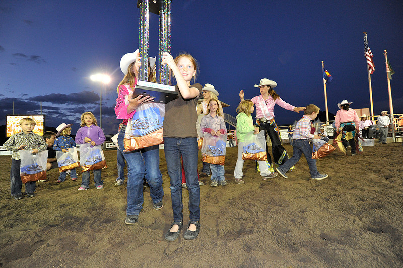 Walt Hester | Trail Gazette<br /> Zoe Theiss, 8, of Estes Park raises the Mutton Bustin' trophy after winning the event on Wednesday night at the Rooftop Rodeo. Each night, a new champion is awarded the huge trophy.