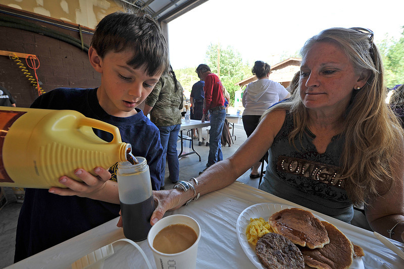 Walt Hester | Trail Gazette<br /> Gabe Housewright pours syrup for hungry visitors to the Glen Haven firehoue fundraiser on Saturday. The town is raising money to build a new firehouse, not far from the current home of the volunteer fire fighters.