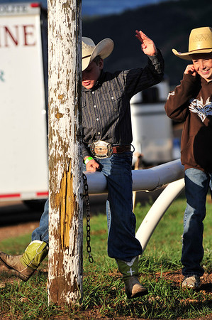 Walt Hester | Trail Gazette<br /> Colten Inskeep, 8, of Greeley, rides the rail at the Stanley Fairgrounds on Saturday, to the cheers of Randy Stark, 10, of Eaton. The two were mimicking their fathers at the Rooftop Rodeo.