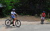 Walt Hester | Trail-Gazette<br /> A pair of cyclists wait for traffic to clear along Hwy 7 on Wednesday morning. Road construction held up cyclists as well as motorists.
