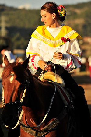 Walt Hester | Trail Gazette<br /> Sarah Morgan of Lakewood holds a flower as sge is bathed in evening light. Spectators were treated to perfect weather as well as a great show on Friday.