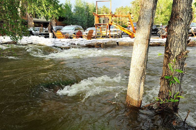 Walt Hester | Trail Gazette<br /> The Fall River laps against sand bags and claims a little new territory below Performance Park on Wednesday. Continued warm weather and afternoon rain has kept the rivers in Estes Park hig enough to garner attention.