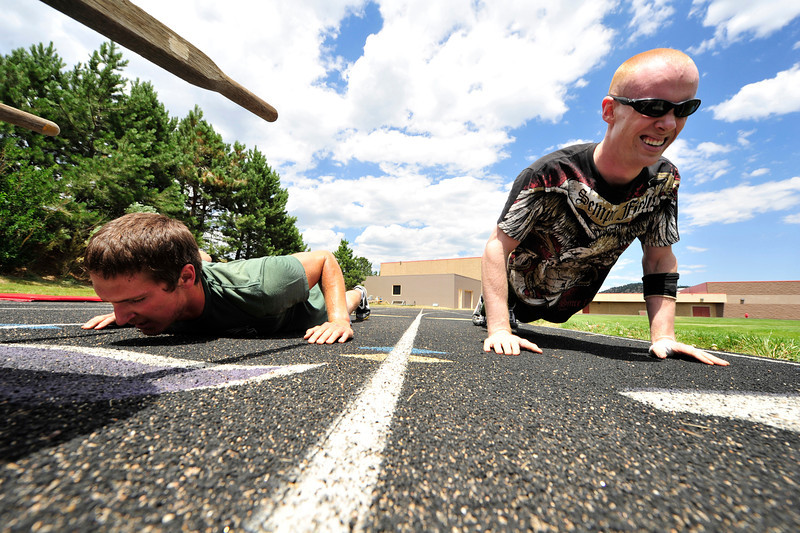 Walt Hester | Trail Gazette<br /> Ben Ekeren, left, and Nathanial Romig crank out 35 push ups after pushing a wheelbarrow around the Bobcats Stadium track on Saturday. Every 100 yards, athletes stopped to perform some exercise before moving on, 400 yards and 140 repetitions in all.