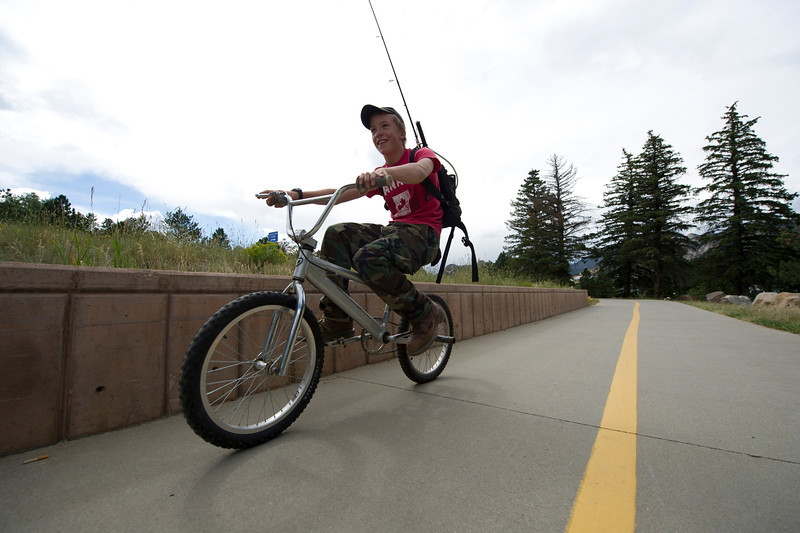 Walt Hester | Trail Gazette<br /> A young, local fisherman makes his way along the Lake Estes Trail last week. For runners, boarders, cyclists and walkers, the trail is a pleasent alternative to driving.