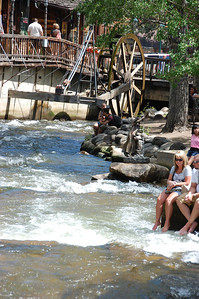 Visitors cool off by dipping their feet in Fall River above the water wheel north of Elkhorn Avenue.