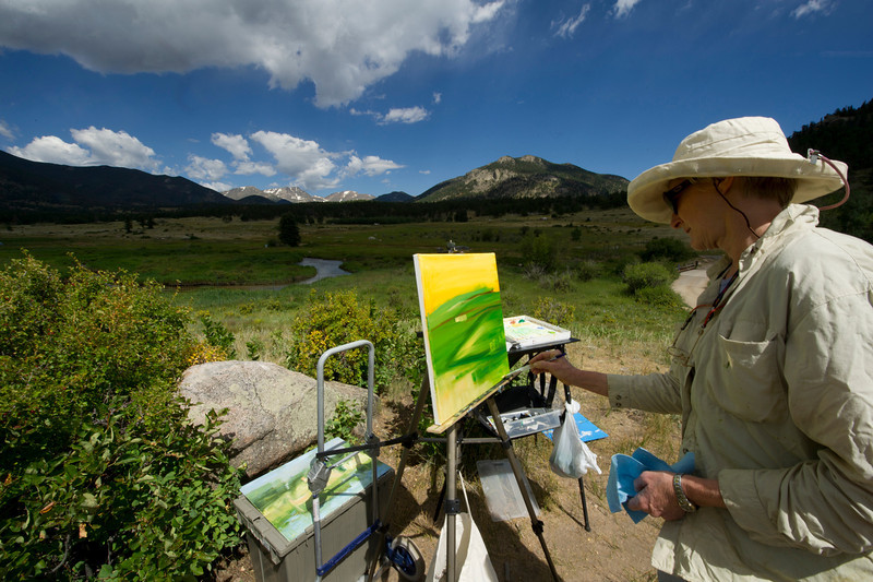 Walt Hester | Trail Gazette<br /> Karen Scharer of Big Elk Meadows begins a scene in Morain Park on Wednesday. The Plein Air painters are out and about in the Estes Park area, painting their way toward the big Quick Draw and show on Saturday, August 27 in Riverside Plaza.