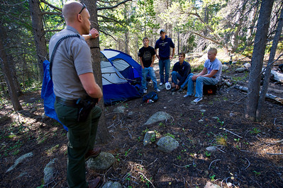 Walt Hester | Trail Gazette Law enforcment ranger Brennon Shaughnessy informs a group of young men that they are camped illegally on Saturday. Most of what he law enforcment rangers see is illegal camping, illegal fire rings, gathering fire wood and the like, though they are called in on search and rescue operations when needed.