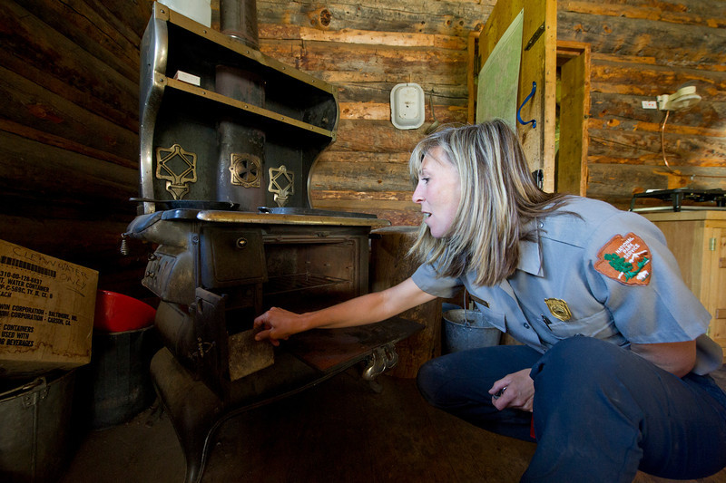 Backcountry ranger Marybeth Lisse checks out an antique stove in the Willow Park Patrol Cabin on Saturday. Their are several backcountry patrol cabins, and part of the job of the wilderness crews is make sure they are all well stocked in case of emergency.