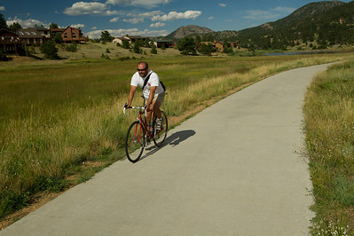 Walt Hester | Trail Gazette Terry Leija of Estes Park enjoys a little saddle time on the trail along Carriage Drive on Tuesday. The trails aroiund Estes Park offer a scenic and safe path for cyclists, runners and walkers.