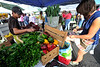 Walt Hester | Trail Gazette<br /> Ty Doering restocks cucumbers as Hannah Cockroft wights prices on a small chockboards at the Estes Valley Farmers Market on Thursday. The market continues on Thursday morning for four more weeks.