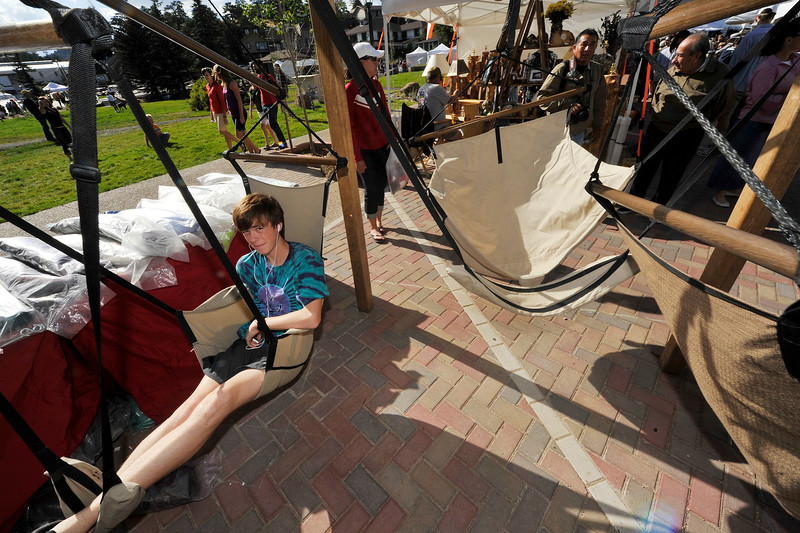 Walt Hester | Trail Gazette<br /> Colin Crawford, 14, of Boulder holds down a hanging chair in his mother's booth at the annaul Labor Day Arts and Crafts Market on Saturday. Small retailers, like the art market boothes, require a whole-family effort, much like traditional small businesses.
