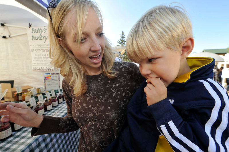 Walt Hester | Trail Gazette<br /> Carter Kemp, 3, of Arvada chomps crackers with homemade jelly with mom, Katie, at the arts and crafts market on Saturday. Along with sculptures, photos and paintings, the market offers goodies and crafts for one's taste buds.
