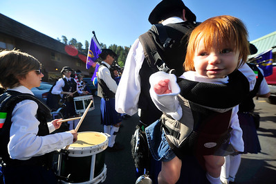 Walt Hester | Trail Gazette Caydence Downs, 1, of Denver, dangles from a hanging baby carrier off of the back of her father, Justin, a drummer for Ciorcal Cairde pipes and drums of Denver. The little redhead's name is Irish Gaelic for Rythmic.