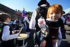 Walt Hester | Trail Gazette<br /> Caydence Downs, 1, of Denver, dangles from a hanging baby carrier off of the back of her father, Justin, a drummer for Ciorcal Cairde pipes and drums of Denver. The little redhead's name is Irish Gaelic for Rythmic.