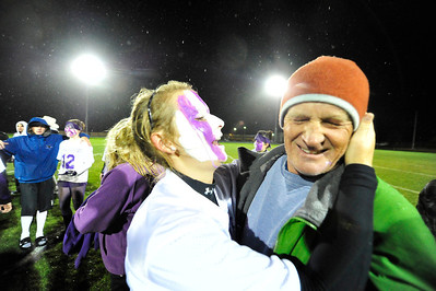 Walt Hester | Trail Gazette Jesse O'Dell plants a wet and paint-smeared kiss on Rick, her father's, cheek on Wednesday. The Homecoming week tradition, the Powder Puff Game, was played in a chilly, soaking rain, and ended with a Seniors win, 37-7.