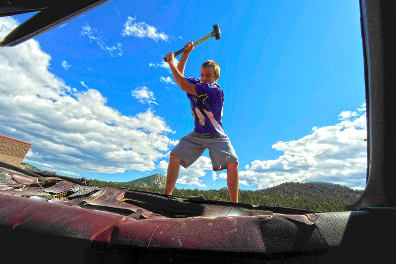 Walt Hester | Trail Gazette<br /> TJ Hall Takes a sledge hammer to an old Suburban during the annual Car Bash at the high school on Friday.