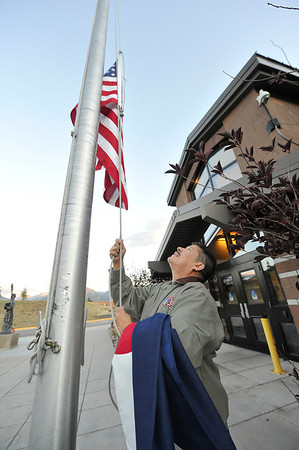 "Walt Hester | Trail Gazette<br /> Raul Arellano of Estes Park hoists the American flag at the Estes Park Elementary School on Wednesday. Arellano says children call him the ""New Miss Aimee."""