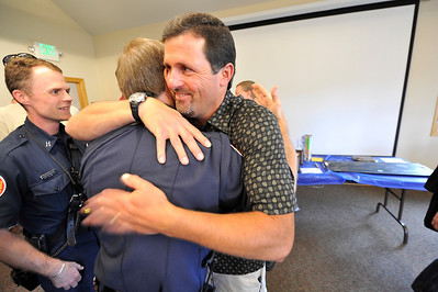 Walt Hester | Trail Gazette Robert Schumaker hugs fire chief Scott Dorman at the farewell event at the Estes Park Museum on Monday. Schumaker leaves the force after 20 years of service to Estes Park.