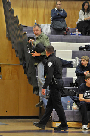 Walt Hester | Trail-Gazette<br /> A Bulldogs' fan leaves the gym with a police escort in the first quarter of the Estes Park boys basketball game against University on Friday night. Neither player, coaches or fans are alowed to taunt at CHSAA events.