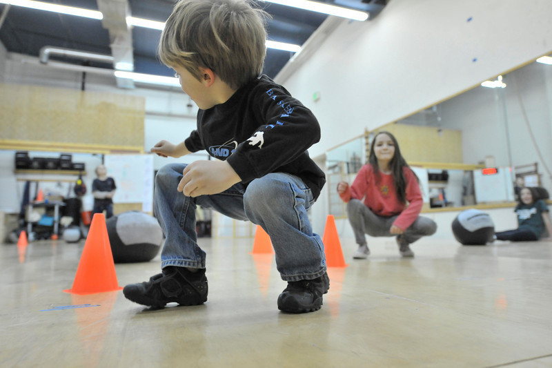 Walt Hester | Trail-Gazette<br /> Children duck walk around a CrossFit version of Musical Chairs on Saturday. CrossFit Kids uses games to develope fitness and coordination.