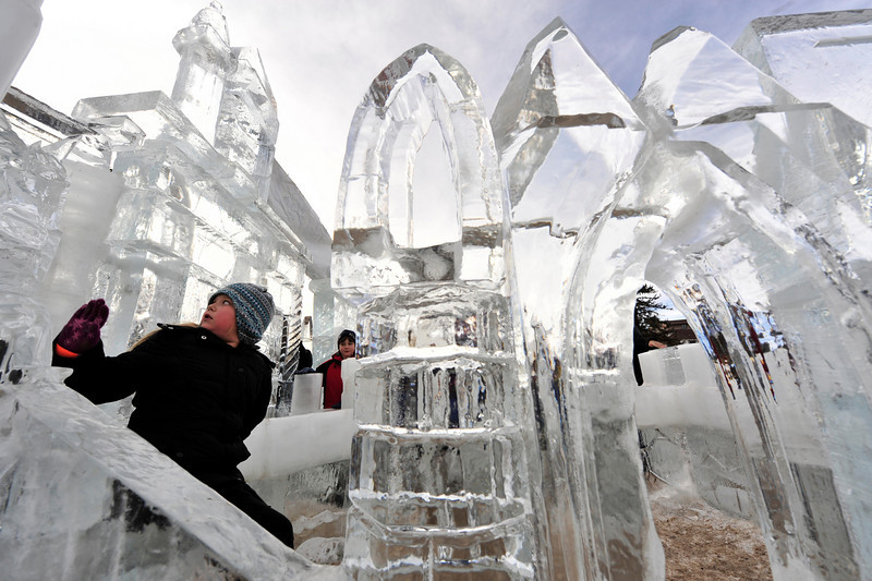 Walt Hester | Trail-Gazette<br /> Victoria Stockton, 7, of Brighton, Colo., sits in the ice castle maze in Bond Park on Saturday. The castle and maze were part of several ice sculptures around the festival.