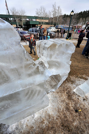 Walt Hester | Trail-Gazette<br /> Wesly Parker, 8, of Colorado Springs tosses a bll through a hole in an ice sculpture in Bond Park on Saturday. The sculpture, as wella s the ice maze, castle and slide were all part of the annual Estes park Winter Festival that ran from Friday through Monday.