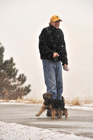 Walt Hester | Trail-Gazette<br /> Bill Cook stands in Wednesday's snow with his two-month-old, soft-coated Wheaton terrier along Lakeshore Drive.
