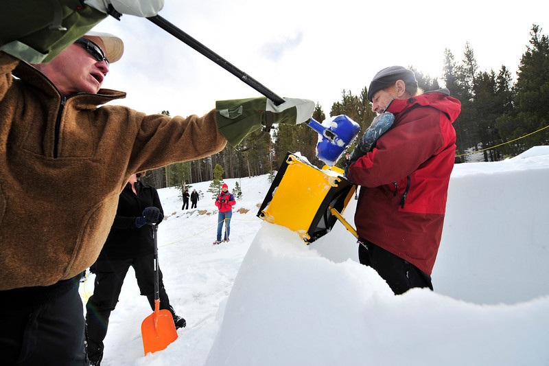Walt Hester | Trail-Gazette<br /> Chris Lord of gypsm shovels snow into an igloo block maker held by Ed Huesers of Lyons at the Winter Trails Day at the Glacier Basin park and ride lot on Saturday.