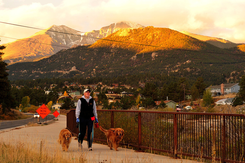 Walt Hester | Trail Gazette<br /> Longs Peak looms over Lee Kennicky and her companions, Kaley and Sunny, on Thursday morning. Though relatively warm, clouds clinging to the high mountains are harbingers of cooler, autumnal weather.