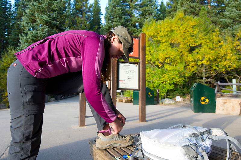 Walt Hester | Trail Gazette<br /> Erika Sidney of Denver laces up at the Bear Lake trail head for a hike on Sunday. Warm, dry weather has tempted crowds away from the urban Front Range and into the national park.