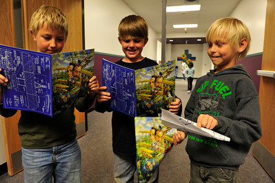 """Walt Hester   Trail Gazette Tanner Leonard, 9, Alexander Henderson, 8, and William Janz, also 8, read their magazines from the historical play """"The Wright Stuff"""" on Wednesday. The play educated the elementary school students about the lives and accomplishments of Orvil and Wilber Wright."""