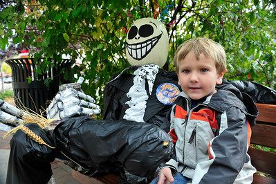 Walt Hester   Trail Gazette Jesse DuPuis, 5, of Cambridge, NY, sits next to a scarecrow along Elkhorn Avenue on Monday. The scarecrow is part of the month-long festival of scarecrows in Estes Park.