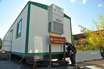 Walt Hester   Trail Gazette Matt Pavelka of the national park works on signage for the trailer in front of the Beaver Meadows Visitor Center building on Thursday. The trailer will serve as the visitor center while the main building is renovated.
