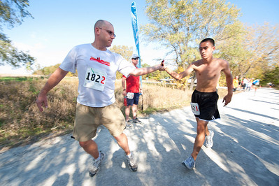 Walt Hester   Trail-Gazette The Spiders from Mars team captain, Tim Woodbury of Omaha takes the timing chip from the team's youngest runner, 15-year-old Brandon Tauzin, for the last time. Teams were made up of between 6-8 members, each running multiple stages.